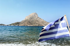 Flag of Greece waving at Telendos island and blue sea background Royalty Free Stock Photos