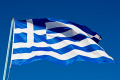 Flag of Greece waving in the wind. Under a clear blue sky, shot from low angle stock photo