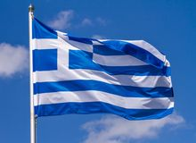 Flag of Greece waving in the wind on flagpole against the sky with clouds on sunny day. Close-up royalty free stock photography