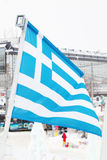 Flag of Greece on wind at winter cloudy day. In street of city Royalty Free Stock Image