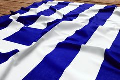 Flag of Greece on a wooden desk background. Silk Greek flag top view.  stock images