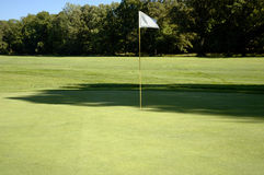Flag on the Green. A white flag on the pin marks this hole on the golf course Royalty Free Stock Photo