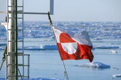 Flag of Greenland - Ships Mast. Flags of Greenland flying from the mast of a tourist icebreaker Stock Photo