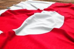 Flag of Greenland on a wooden desk background. Silk flag top view.  stock photos