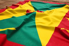 Flag of Grenada on a wooden desk background. Silk Grenadian flag top view.  royalty free stock photo