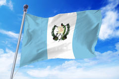 Flag of Guatemala developing against a clear blue sky. On a sunny day stock image