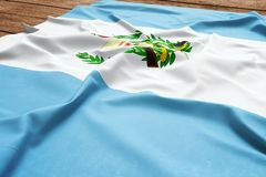 Flag of Guatemala on a wooden desk background. Silk Guatemalan flag top view.  stock image