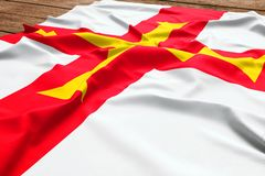 Flag of Guernsey on a wooden desk background. Silk Guerns flag top view.  stock photos