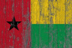 Flag of Guinea Bissau painted on worn out wooden texture background.  stock photo