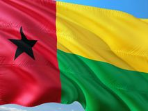 Flag of Guinea Bissau waving in the wind against deep blue sky. High quality fabric.  royalty free stock photography