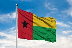 Flag of Guinea Bissau waving in the wind against white cloudy blue sky. Guinean flag.  royalty free stock image
