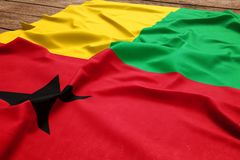 Flag of Guinea Bissau on a wooden desk background. Silk flag top view.  stock images
