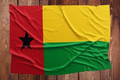 Flag of Guinea Bissau on a wooden table background. Wrinkled Guinea Bissauan flag top view.  royalty free stock photos