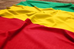 Flag of Guinea on a wooden desk background. Silk Guinean flag top view.  stock photos