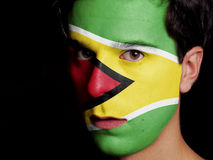 Flag of Guyana. Painted on a Face of a Young Man Royalty Free Stock Photo
