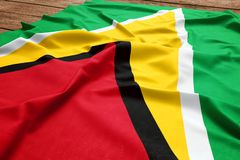 Flag of Guyana on a wooden desk background. Silk Guyanese flag top view.  royalty free stock photo