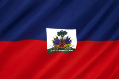 Flag of Haiti - Caribbean. The national flag of Haiti. The coat of arms depicts a trophy of weapons ready to defend freedom and a royal palm for independence stock photo