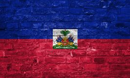 Flag of Haiti over an old brick wall background, surface royalty free stock photo