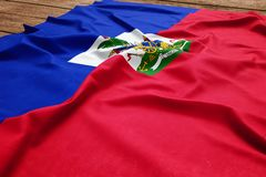 Flag of Haiti on a wooden desk background. Silk Haitian flag top view.  royalty free stock photography