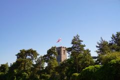 Church tower and half mast flag. English village church tower among tree`s and flying the flag of St George at half mast Stock Photo