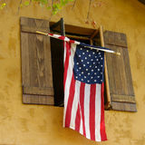 Flag hanging from shutters Royalty Free Stock Photography