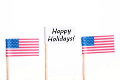 Flag with Happy Holidays. A White Flag with Happy Holidays and Two American Flags Beside, Isolated Royalty Free Stock Image