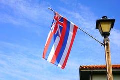 Flag of Hawaii floating on a blue sky. Flag of Hawaii floating on a mast on a blue sky stock image