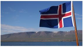 Flag of Iceland. Icelandic flag waving in the wind with icelandic nature in the background Stock Photo