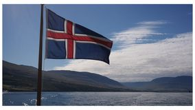 Flag of Iceland. Red and blue flag of Iceland waving in the wind and icelandic nature in the background Royalty Free Stock Image