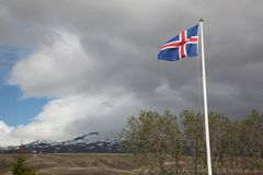 Icelandic Flag Blowing in the Wind on a Stormy Day. Flag of Iceland standing prominently, waving in the wind on a stormy day in the mountains stock image
