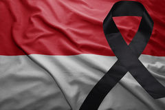 Flag of indonesia with black mourning ribbon. Waving national flag of indonesia with black mourning ribbon Stock Photos