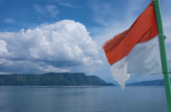 Flag of Indonesia, Lake Toba, North Sumatra. Flag of Indonesia flying with cloudy landscape at the background, Lake Toba, North Sumatra royalty free stock images
