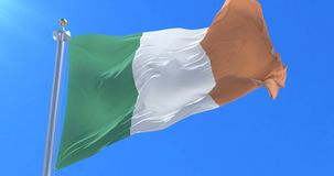 Flag of Ireland waving at wind in slow in blue sky, loop. Ed stock footage