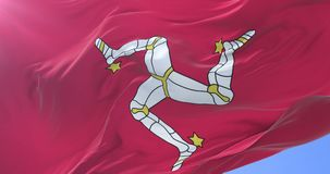 Flag of the Isle of Man waving at wind with blue sky in slow, loop. Ed stock footage