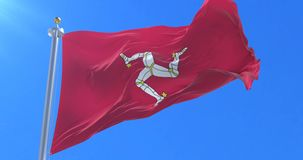 Flag of the Isle of Man waving at wind in slow in blue sky, loop. Flag of the Isle of Man waving at wind with blue sky in slow, looped stock footage