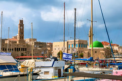 Flag of Israel against the background of growing old Acre. The left is the clock tower inn Al Umda Royalty Free Stock Image