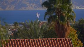Flag Of Israel fluttering against the blue sea stock video footage