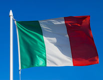 Flag of Italy. Against blue sky during wind Stock Image