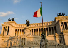 Flag of Italy and Altare del Patria on the background. Victor Emmanuele II memorial and Italian Flag in Rome lit by the soft evening sun Royalty Free Stock Image