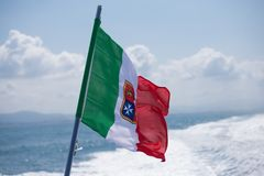 Flag of Italy with the coat of arms. Over the blue sea Stock Photo