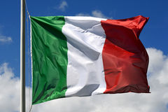 Flag of Italy fluttering in the wind. Against a cloudy sky, concept of italian national pride and identity stock image