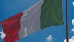 Flag of Italy waving in wind proudly, blue sky background, national symbol. Stock footage stock footage