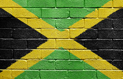 Flag of Jamaica on brick wall. Flag of Jamaica painted onto a grunge brick wall royalty free stock photography