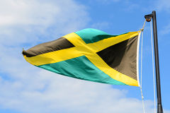 Flag of Jamaica. Waving against blue sky.  have a gold saltire on a green and black field stock photo