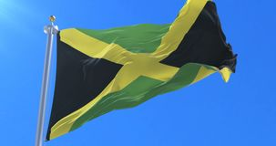 Flag of Jamaica waving at wind with blue sky in slow, loop. Ed stock illustration