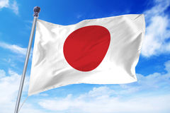 Flag of Japan developing against a clear blue sky Stock Photos