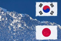 The flag of Japan and South Korea are painted at opposite end of piece of ice in the form of an arctic iceberg against blue sky. Cold war, warming background stock images