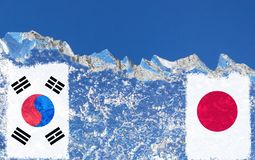 The flag of Japan and South Korea are painted at opposite end of piece of ice in the form of an arctic iceberg against blue sky. Cold war, warming background royalty free stock photo