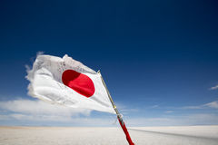 Flag from Japan waving in the Salar of Uyuni, Bolivia Royalty Free Stock Photos