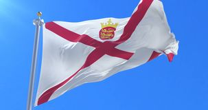 Flag of Jersey waving at wind with blue sky in slow, loop. Ed stock footage